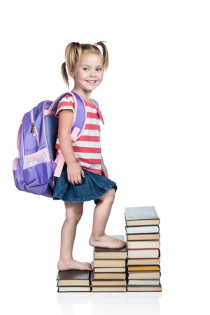 učebnice: Little beautiful schoolgirl with a backpack on his back climbing up the stairs of books isolated on a white background
