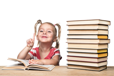 Portrait of a beautiful child girl with a book at the table, lifted the index finger up, isolated on a white background