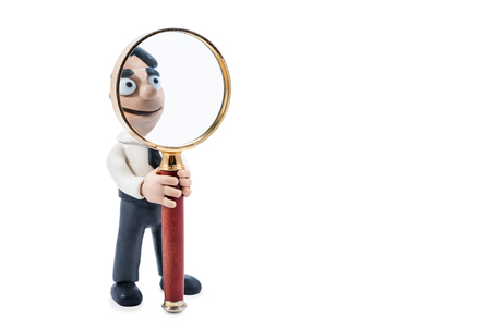 Plasticine businessman holds a magnifying glass in hands, isolated on a white background Stock Photo