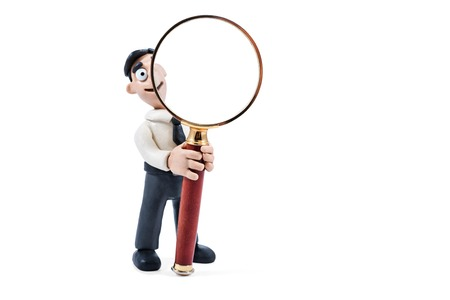 Plasticine zakenman op zoek in vergrootglas geïsoleerd op een witte achtergrond Stockfoto