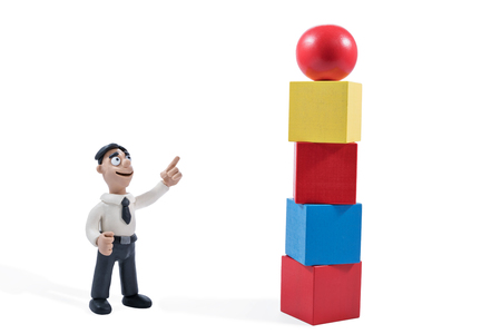 Plasticine businessman points to a toy tower from wooden blocks with the ball at the top isolated on white background