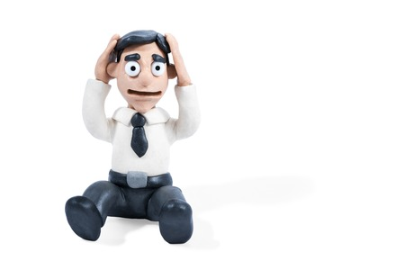 Frustrated plasticine businessman sitting on the floor and holding his head, isolated on white background