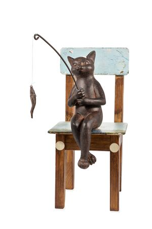 fishing village: Bronze figure of a cat with fishing rod sitting on an old wooden chair isolated on a white background