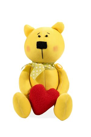 Beautiful yellow fabric toy bear with heart in hand isolated on white background