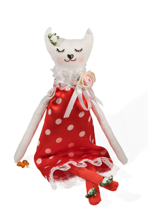 Handmade stuffed cat in red dress with polka dots with closed eyes isolated on white background