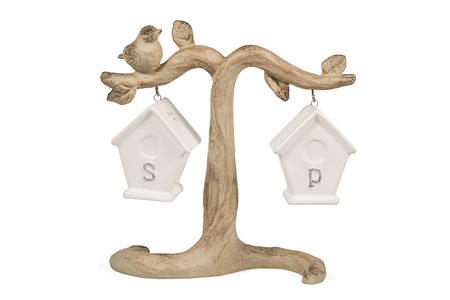 Pepper and salt shaker in the form of ceramic houses hanging on a tree with a bird isolated on a white background