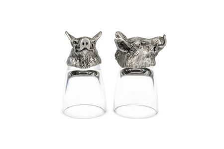 Two inverted glasses for vodka with a bottom in the shape of a head of a wild boar isolated on white background