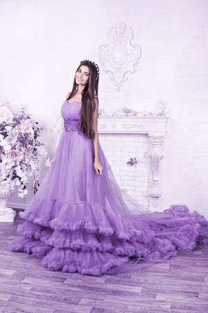Toned portrait of a beautiful lady in a long ball gown with a hem