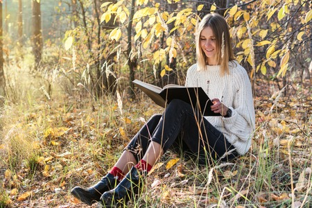 black sweater: Beautiful woman in a sweater is reading a book sitting on the grass in an autumn forest