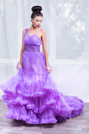 Portrait of a beautiful woman in a purple ball dress at the window