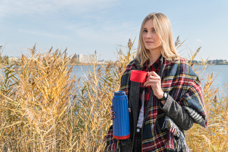 Beautiful blonde woman drinks tea from a thermos at the lake overgrown with reeds