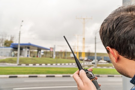 Man holds a walkie-talkie in his hand and stares into the distance at a blurry road in the background, a back view Banque d'images