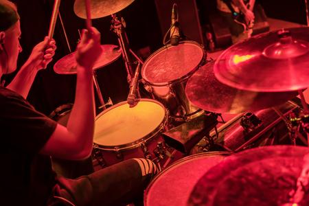 Drummer verslaat de drums tijdens een concert in rood licht