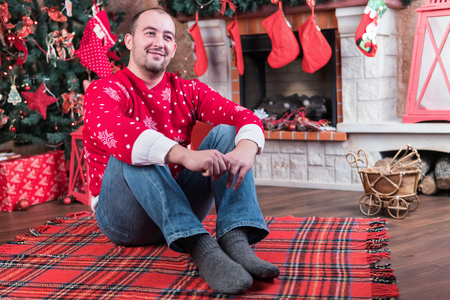 Smiling man in a red sweater sitting by the fireplace with a Christmas tree