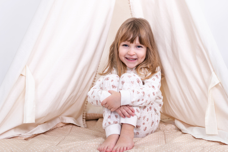 Portrait of a little smiling girl sitting on the floor near the tent and hugging her knees