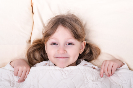 Portrait of a little beautiful girl poking her head out from under the blankets Foto de archivo
