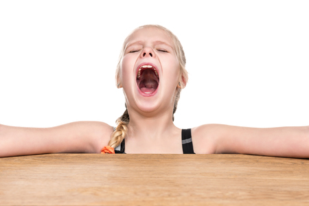 Little girl sitting at table with hands to side and screaming isolated on white background Stockfoto