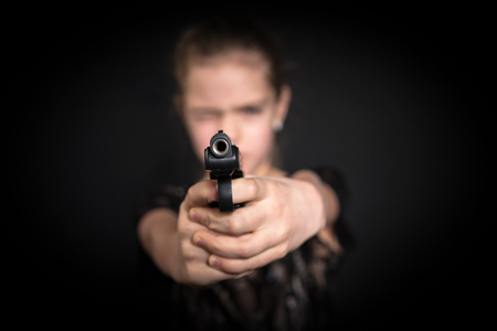 Girl aiming a gun at the camera, blurred background, on black Stock Photo