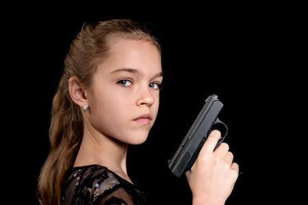 Close-up portrait of a young girl with a gun in her hand isolated on a black background