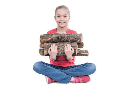 Girl sitting with legs crossed and holding pile of firewood, looking up at camera isolated on white background Stock Photo