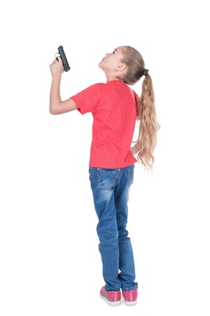 Young girl is standing with her back to the camera and aiming a gun up, isolated on a white background