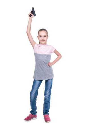 Young cute girl lifted a gun up, isolated on a white background