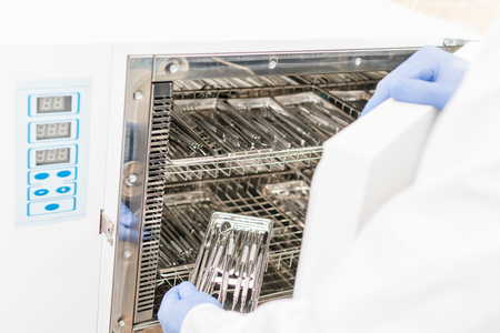 Dentist opened the door of the sterilization cabinet and loads the instruments Standard-Bild