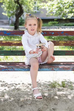 Beautiful little girl sitting on an old bench shakes the sand out of the flip-flops