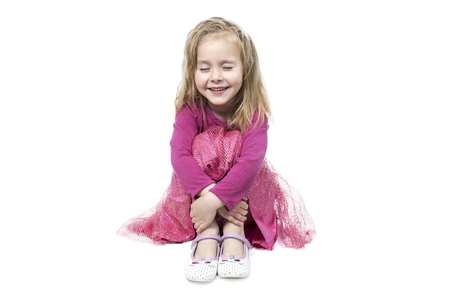 Portrait of a small beautiful, smiling girl with closed eyes sitting on the floor and hugging her knees isolated on a white background