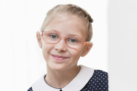 Portrait of a beautiful girl in glasses and a dress in peas on white
