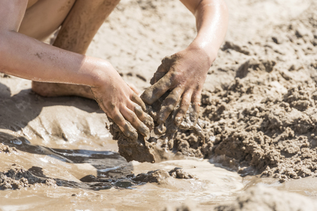 Children hands are digging in wet dirty sand