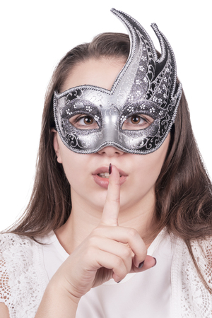 Woman in gray mask holds forefinger at mouth, isolated on white background