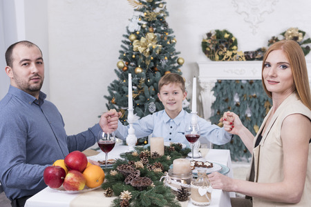 Family sitting at christmas table by the Christmas tree and holding hands Standard-Bild