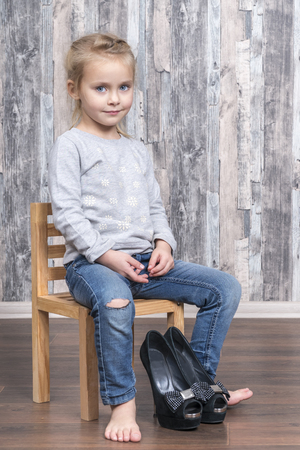 child is sitting on a chair and prepared to put on her mother high-heeled shoes
