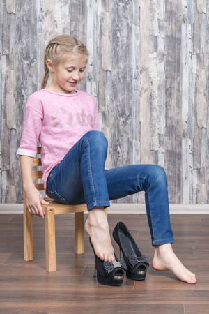 little beautiful girl sits on a chair and wears black mother high-heeled shoes Stockfoto