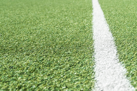 Football field with artificial grass and a white line on the side, stretching into the distance