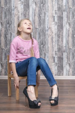 Niña sentada en una silla de madera parece frustrada probándose los zapatos de tacón de su madre