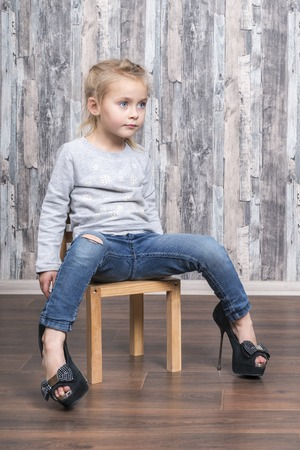 baby girl sitting on a wooden chair, legs wearing her mother big shoes Zdjęcie Seryjne