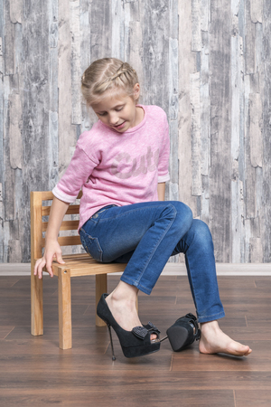 girl sits on a wooden chair and looks at her leg dressed in large mother high-heeled shoes