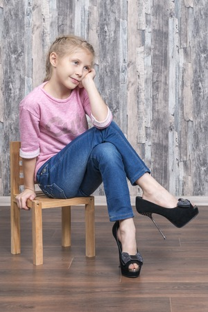 Young beautiful girl in her mother shoes sits on a small wooden chair and dreams of leaning on her arm