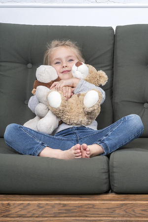 Little girl sitting on the couch, two hands hugging soft toys