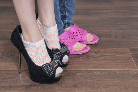 Two children put on shoes, one of her mother shoes with heels, the other pink flip flops, close-up Standard-Bild