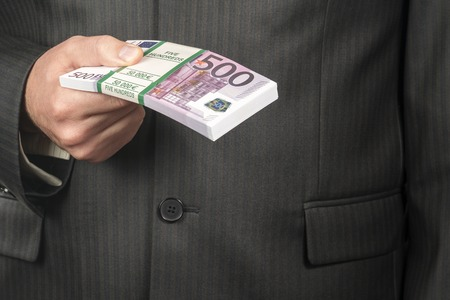 businessman in suit holding a bundle of money with a face value of five hundred euro, closeup