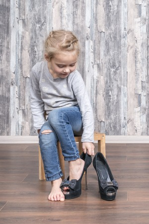child wears her mother shoes on the leg while sitting on a small wooden chair