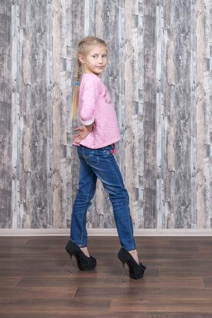 La giovane bella ragazza in jeans è alla moda davanti alla macchina fotografica nelle sue scarpe della madre