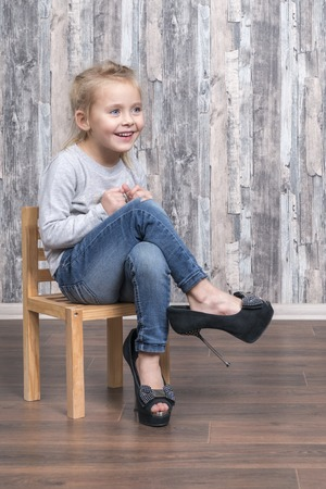 Cheerful little girl is sitting on a wooden chair and wearing her mother shoes Archivio Fotografico