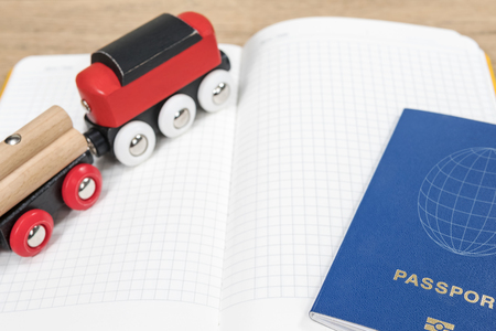 Concept planning an overseas trip by train with a toy train, a passport and diary