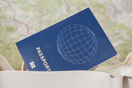 blue passport sticks out of a white female bag on a blurred map background