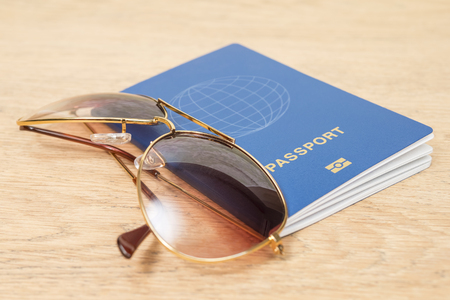 sunglasses and a biometric passport on an old wooden table