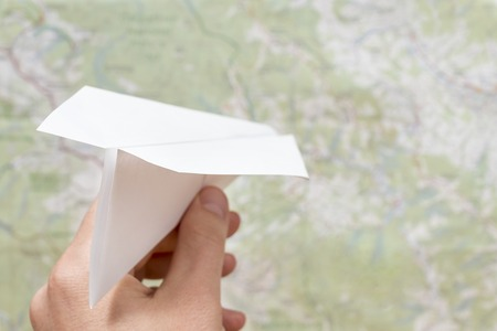 male hand launches a paper plane on the background of the map